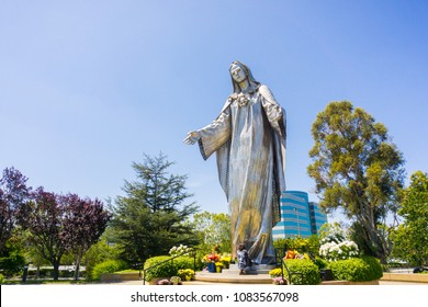 May 3, 2018 Santa Clara / CA / USA - Woman praying at the base of the Virgin Mary statue at Our Lady of Peace Roman Catholic Shrine in the parish of the Diocese of San Jose, California