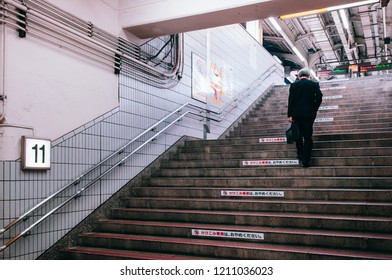 MAY 30, 2013 Nagoya, Japan - Japanese man in office uniform walking up on stair to platform at Nagoya train station - Vintage film image style