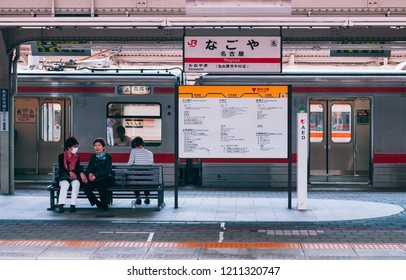 MAY 30, 2013 Nagoya, Japan - Passengers waiting at platform of JR Nagoya station with station sign and local train in background - vintage film style image