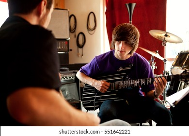 May 4, 2010. Eugene, Oregon, USA.  A teenage boy learning to play the electric guitar at a local music store.