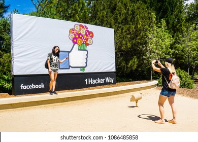 May 8, 2018 Menlo Park / CA / USA - A girl posing in front of the Facebook Like Button sign (customised for Mother's Day), located at the entrance to the company's main headquarters, Silicon Valley