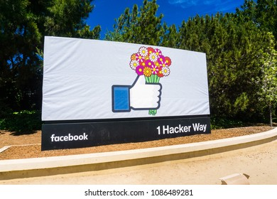 May 8, 2018 Menlo Park / CA / USA - The Facebook Like Button sign holding a bouquet of flowers (celebrating Mother's Day) located at the entrance to the company's main headquarters in Silicon Valley