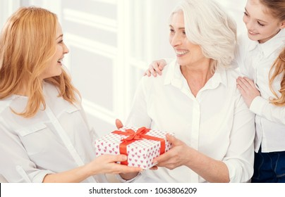 May all your dreams come true. Adorable moment of loving grandmother and grandchild smiling to a beautiful mother while congratulating her and giving her a beautifully wrapped gift.