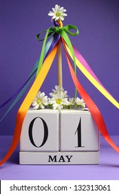 May Day, May 1, white block calendar with maypole and rainbow color ribbons and flowers against a purple background.