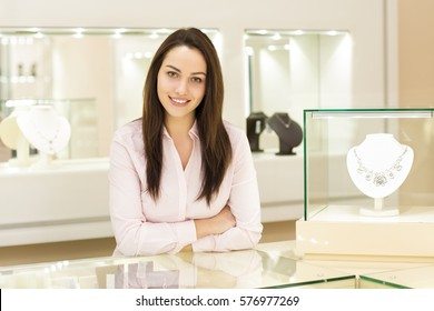 May I help you? Beautiful female jeweler smiling standing behind the showcase counter at jewelry store business businesswoman assistant helpful profession professional job occupation service concept