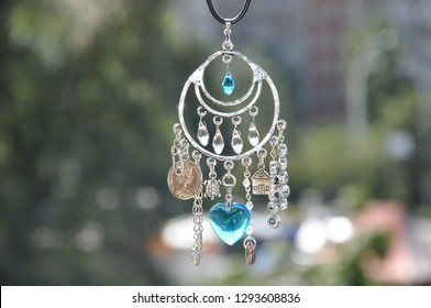 May the luck be with you. Luck amulet hung out outdoor. Name amulet for good luck. Silver amulet with gems and pendants. Believing in magic protecting the holder of amulet. Jewelry charm or talisman.