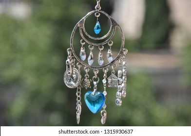 May luck be yours. Jewelry charm or talisman. Name amulet for good luck. Luck amulet hung out outdoor. Silver amulet with gems and pendants. Believing in magic protecting the holder of amulet.