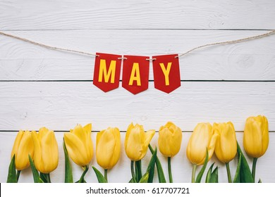 May paper garland lettering, text, letters, inscription. Yellow tulips border frame on white wooden planks rustic barn rural table background. Beautiful horizontal flat lay spring postcard.