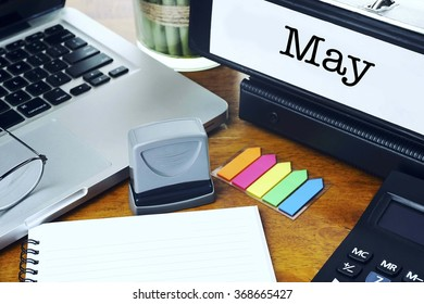 May- Ring Binder on Office Desktop with Office Supplies. Business Concept on Toned and Blurred Background
