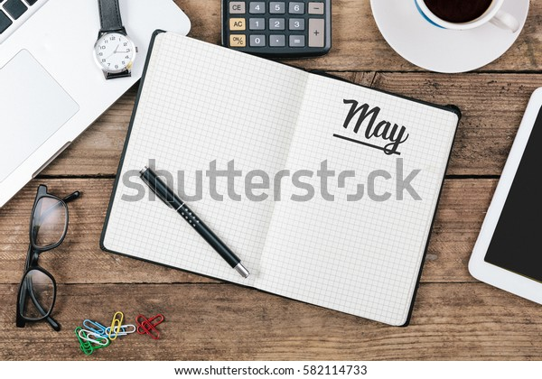 May text in note book on office desk with electronic devices, computer and paper, wood table from above, concept image for blog title or header image.