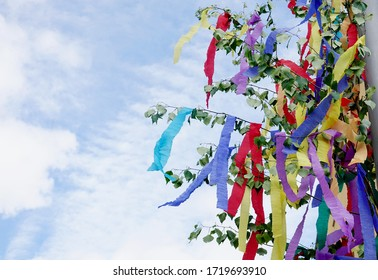 May tree with colored ribbons against sky copyspace First of May tradition in Germany