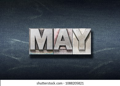 May word made from metallic letterpress on dark jeans background