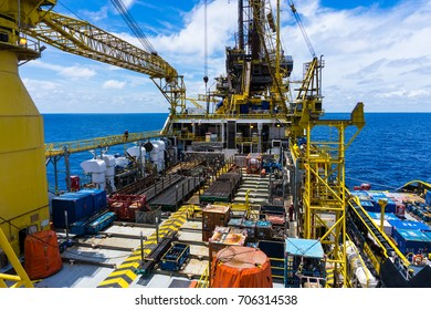May-20, 2017 - Gulf of Thailand. A supply boat alongside the tender barge oil drilling rig to transfer drilling equipment and bulk products. The storage area is