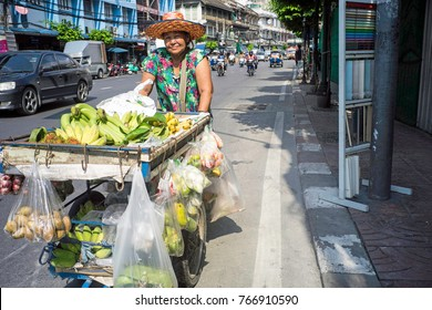 may2017, Bangkok, Thailand, female street seller pedestrian pushes  her cart loaded with bananas and citrus fruits on the side of a main road