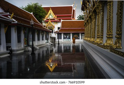 May2017, Bangkok, Thailand,monastery compound after a heavy downpour with the sun shining again, reflections and the gold columns and roof spires shining bright