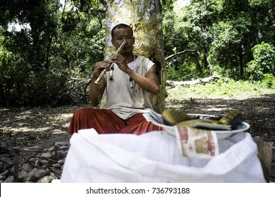 May2017, Lao PDR, Vientiane, man playing a nose flute sits in front a gold painted tree and he collects money from listeners in his bowl in front of him