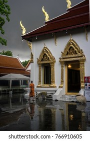 May2017,Bangkok, Thailand,a monk walks oassed a temple after a heavy downpour and the sun illuminates the golden roofspires
