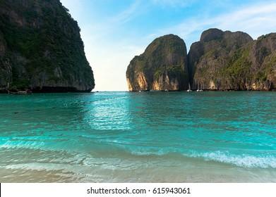 Maya Bay heavenly beach on a background of blue sky and azure sea and amazing limestone rocks, Phi Phi Islands, Thailand