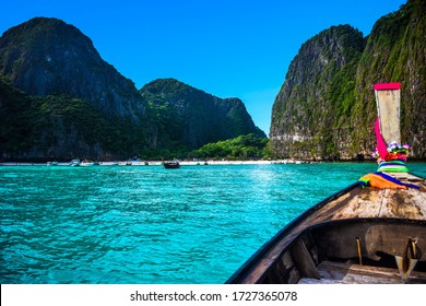 Maya bay hidden phi phi island in Thailand paradise with longtail boat turquoise water blue sky mountains green vegetation white beach