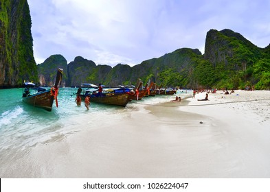 Maya Bay, Koh Phi Phi Leh, Thailand - October 25, 2013. Long tail boats mooring in the famous Maya Bay with tourists on the beach