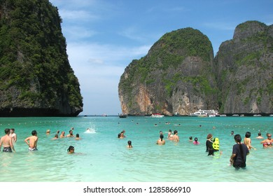 Maya Bay, Thailand - December 7, 2013: Tourists and boats on the famous beach in Maya Bay on Phi Phi islands. Tourists enjoy the white sand Maya Bay beach and turquoise water of lagoon