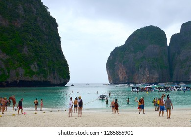 Maya Bay, Thailand - November 28, 2017: Tourists and boats on the famous beach in Maya Bay on Phi Phi islands. Tourists enjoy the white sand Maya Bay beach and turquoise water of lagoon