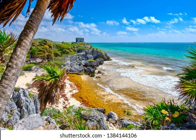 Mayan ruins on top of a cliff and a beautiful tropical beach at the Tulum archeological site in Mexico