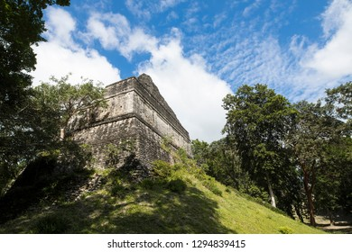 The Mayan Temple of Dzibanche in the forest of Mexico with blue sky behind.