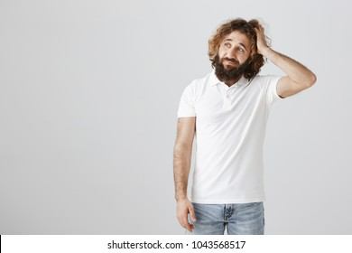 Maybe I should say sorry for my behaviour. Portrait of troubled attractive eastern male with curly hair and beard looking aside with puzzled expression, scratching head, being clueless over gray wall