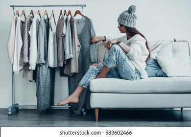 Maybe this one?  Thoughtful young woman in casual wear choosing the dress while sitting on the couch at home near her clothes hanging on the racks