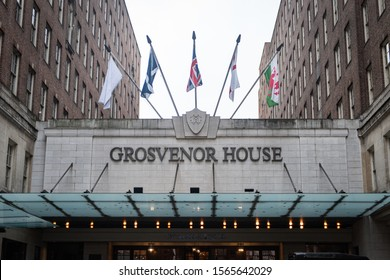 Mayfair, London/UK - November 3 2019: Front facade of the Grosvenor House hotel in central London. Five flags stand out against the grey sky. Glass cantilever extends over the front.