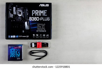 Maykop, Russia - November 9, 2018: Asus motherboard in box, processor intel I3, RAM Kingston Fury HyperX 16 GB and cable for connecting devices SATA 6Gbs on a gray background top view with copy space