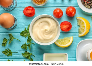 Mayonnaise in bowl with ingredients on wooden background, top view