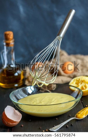 Mayonnaise, egg, spoon with mustard, olive oil and a metal whisk on a dark background.