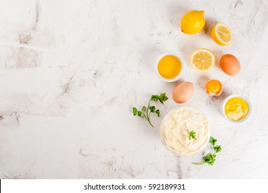 Mayonnaise with ingredients for cooking - eggs, vegetable oil, mustard, lemon, parsley. On the white stone concrete table top view copy space