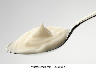 mayonnaise on a spoon with white background