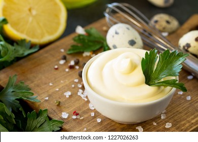 Mayonnaise Sauce close-up. Homemade mayonnaise sauce in a white bowl on black stone or concrete background.