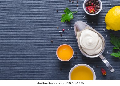 Mayonnaise sauce and ingredients on blue cloth background.
