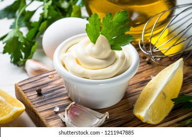 Mayonnaise sauce and ingredients on white. Close up.