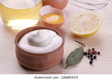 Mayonnaise in a wooden bowl and ingredients for making mayonnaise on a natural wooden background. white sauce.