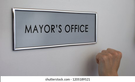 Mayor office door, hand knocking, municipal government official, authority