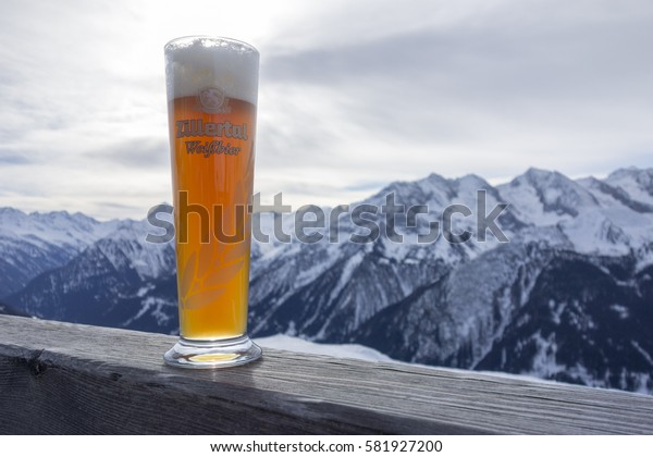 MAYRHOFEN ZILLERTAL, AUSTRIA - february 4 2017: A Glass Zillertal Weissbier on wood with mountains in background. Brewed by Zillertaler Brauerei, oldest privat brewery of Austria