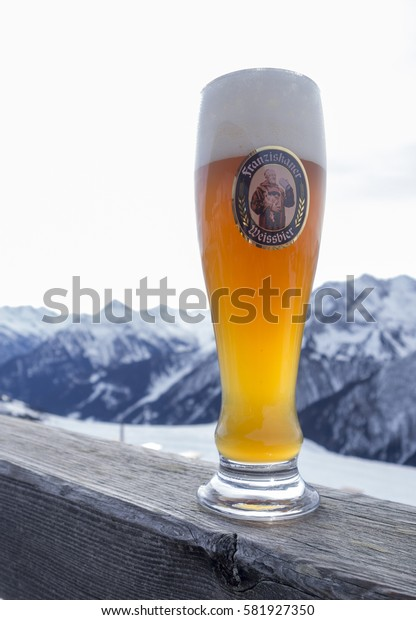 MAYRHOFEN ZILLERTAL, AUSTRIA - february 4 2017: A Glass Franziskaner Weissbier on wood with mountains in background. Brewed by Braustatt bey den Franziskanern in Munich, Germany