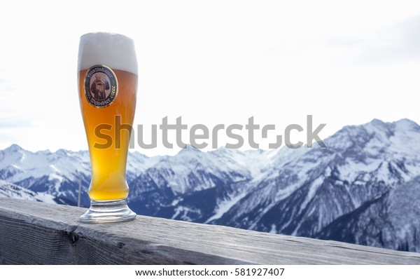 MAYRHOFEN ZILLERTAL, AUSTRIA - february 4 2017: A Glass Franziskaner Weissbier on wood with mountains in background. Brewed by Braustatt bey den Franziskanern in Munich, Germany