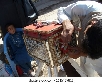 Mazar e Sharif, Afghanistan - June, 2012.  Street photographer. Missing craft. The photographer has a camera on his tripod that also serves as a darkroom. In 5 min. after the Exposition, the photo is