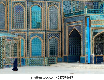 MAZAR-I-SHARIF, BALKH PROVINCE, AFGHANISTAN - 10 MARCH 2013: An unidentified woman walks across the courtyard in front of the Blue Mosque on March 10, 2013 in Mazar-i-Sharif