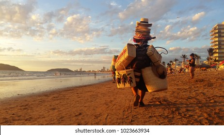 Mazatlan, Sinaloa / Mexico - January 1 2017: A person walks on the beach while carrying sun hats and bags to be sold. Working on the beach is a common informal job in Mexico.