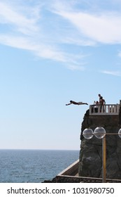Mazatlan/MX: March 16, 2017 – Cliff diver, also known as el clavadista, on the Malecon jumps from 50 foot high platform into water that is five feet deep. Tourists with cameras on platform watch.