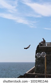 Mazatlan/MX: March 16, 2017 – Cliff diver, also known as el clavadista, on the Malecon swan dives from 50 foot high platform into water that is five feet deep. Tourists with cameras on platform watch.