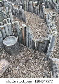 A maze in a playground made out of wooden posts